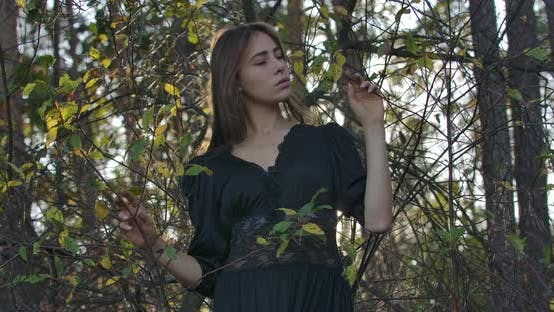 Thumbnail for Thoughtful Brunette Caucasian Girl with Brown Eyes Standing in the Forest in the Evening and Looking