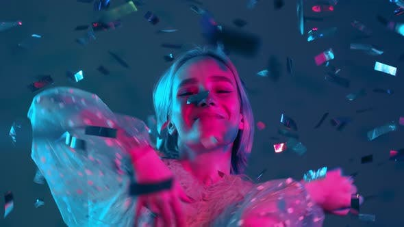 Thumbnail for Young Hipster Woman Dancing, Having Fun, Rejoices Over Confetti Rain with Neon Light in Studio. Dyed
