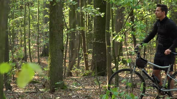 Thumbnail for A Cyclist Stands with a Bicycle in a Forest and Looks Around, Lost