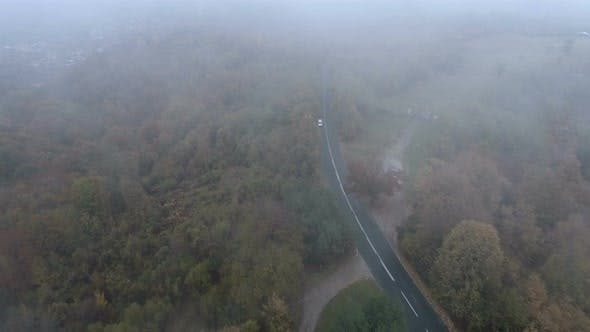 Thumbnail for Drone Follows White Car Driving on Foggy Mountain Road in the Autumn