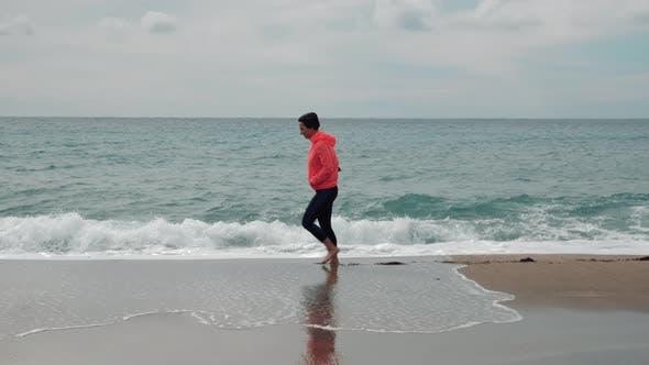 Lonely female is walking on sandy beach