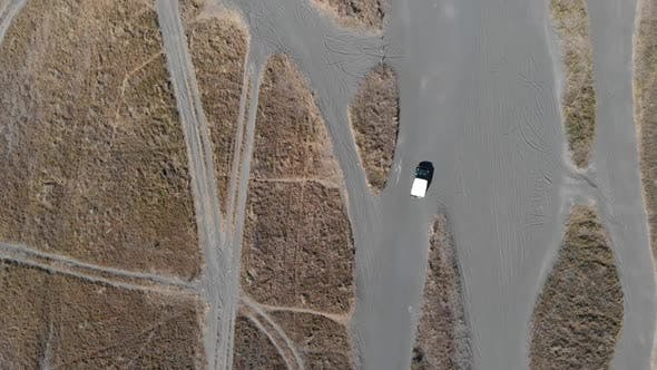 Thumbnail for Cinematic overhead aerial view of off road car tour cruises on sea of sand desert.