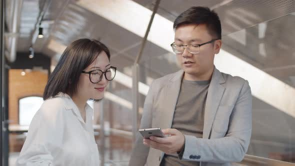 Thumbnail for Two Asian Businesspeople Using Phone
