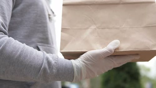 The courier delivers the parcel to the doorstep. Food delivery during the coronavirus pandemic
