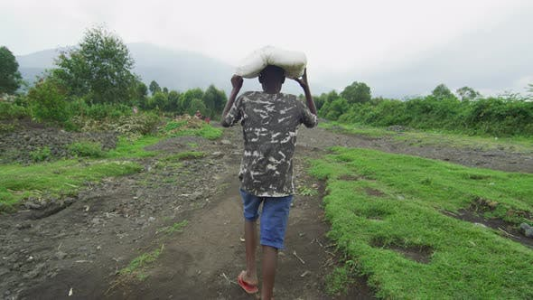 Thumbnail for African boy carrying a sack on his head