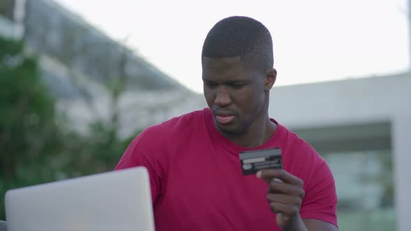 Thumbnail for Afro-American Man Typing on Laptop, Paying with Credit Card