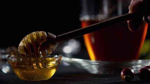 Thumbnail for Adding Some Honey To the Tea Using a Wooden Honey Dipper,