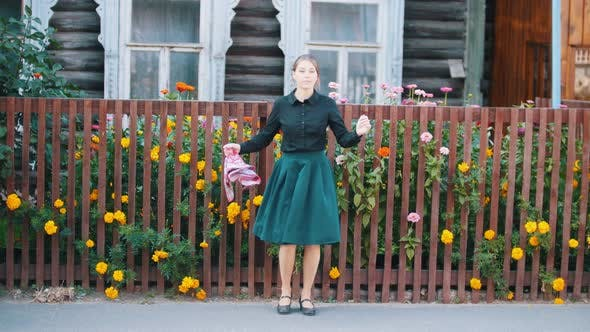Thumbnail for A Young Pretty Woman in Skirt Dancing By the Fence Holding Handkerchief