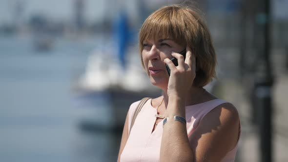 Thumbnail for Fröhlich blonde Frau stehend und reden auf ihrem Smartphone bei Dnipro im Sommer