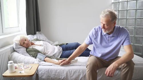 Elderly Woman Is Lying on a Bed and Is Ill and Her Husband Is Sitting Next To Her and Supporting His