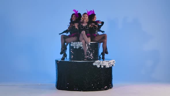 Thumbnail for Gorgeous Sexy Burlesque Dancers Playfully Pose Next To a Large Black Cake