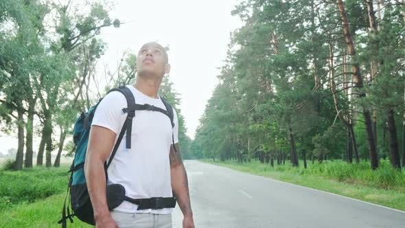 Thumbnail for Handsome African Man Hitchiking on Countryside Road with Backpack