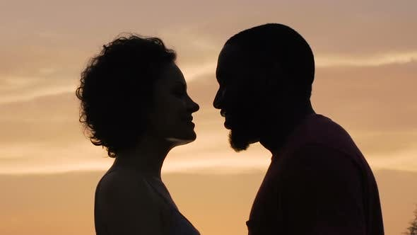 Cover Image for Silhouettes of Man and Woman Gently Touching Each Other Sunset Background