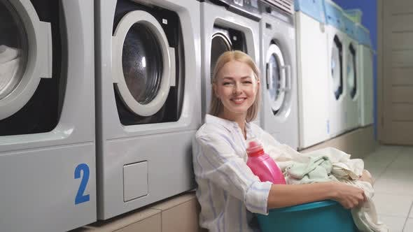 Portrait of an Attractive Blonde Woman in a Public Laundry Room Next To a Washing Machine Holding a