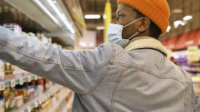 Black Man in Blue Disposable Face Mask Gathers Products
