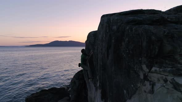 Thumbnail for Aerial Of Man Rock Climbing By Ocean With Colorful Sunset