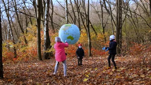 Two girls and a small boy in medical masks play in the autumn Park with a large inflatable ball