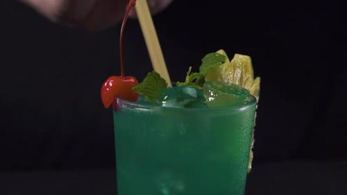 Bartender's Hand Putting a Drinking Straw in a Glass of Green Tropical Cocktail.