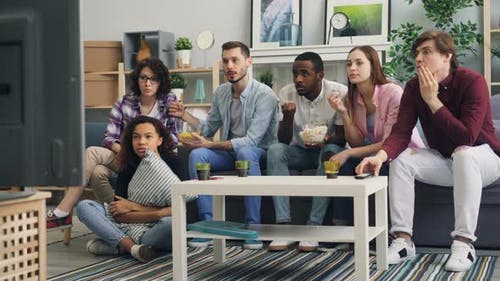 Girls and Guys Chatting at Home Then Watching News on TV Discussing Tragedy