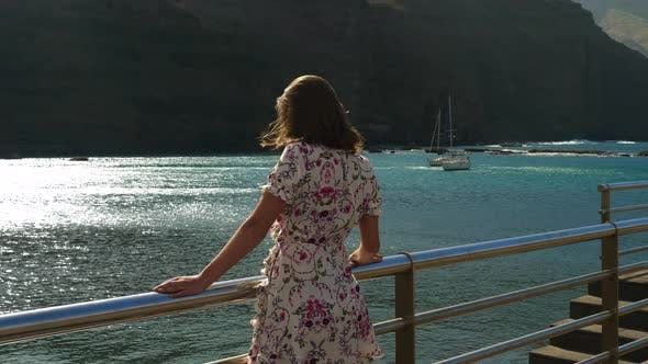 Thumbnail for Beautiful Model by the Hand Railings Looking at a Couple of Sailboats