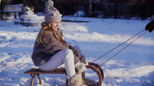 Smiling Young Girl Riding on Sleigh on Winter Vacation. Happy Teen Girl Sledding on Snow While