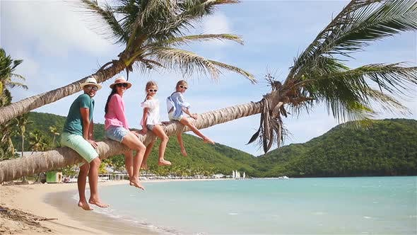 Thumbnail for Young Family on Beach Vacation on Palm Tree. Parents and Kids Having Fun Together on the Coast of