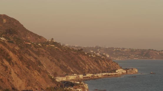 Thumbnail for Helicopter aerial birds eye view shot moving down where shore meets PCH highway, sundown