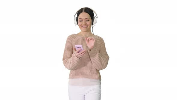 Thumbnail for Happy Girl Walking Listening To Music with Smart Phone Wearing Headphones on White Background.