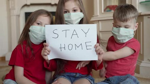 Family Stay at Home Concept. Three Children in Mask Holding Sign Saying Stay at Home for Virus