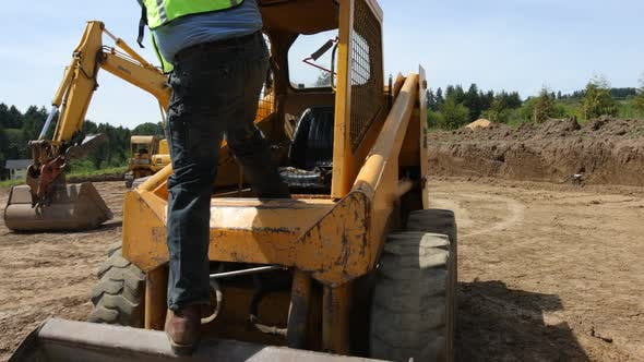 Thumbnail for Worker climbs into skid steer excavator