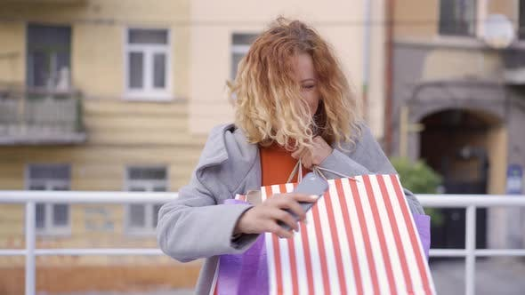 Thumbnail for Excited Red-haired Girl with Shopping Bags and Cellphone in Hands Walking on Air. Adult Woman
