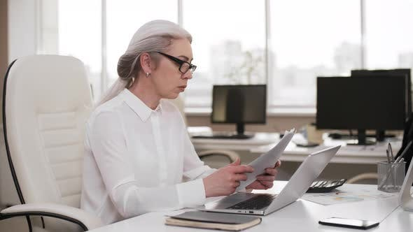 Thumbnail for Grey-haired Business Lady Working on Laptop in Office on Weekend