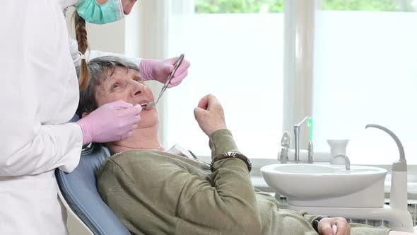 Thumbnail for Elderly woman showing aching tooth to female dentist