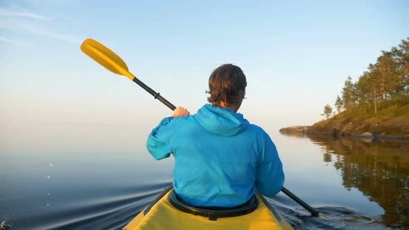 Thumbnail for Outdoor Activities, Man in Slowly Rowing Oars in Kayak on Calm Lake Between Islands