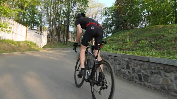 Strong cyclist cycling uphill on a bicycle