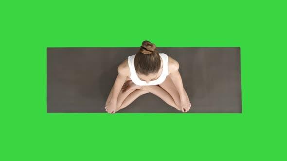 Cover Image for Junge sportliche Frau praktiziert Yoga sitzend in Lotus Pose und Atmung tief auf einem grünen Bildschirm