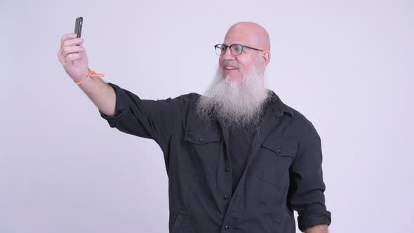 Thumbnail for Happy Mature Bald Bearded Man Smiling While Taking Selfie