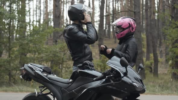 Thumbnail for Side View of Confident Motorbiker Putting on Helmet and Loving Girlfriend Fastening It. Young