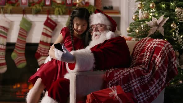 Santa Claus takes cell phone selfie photo with girl