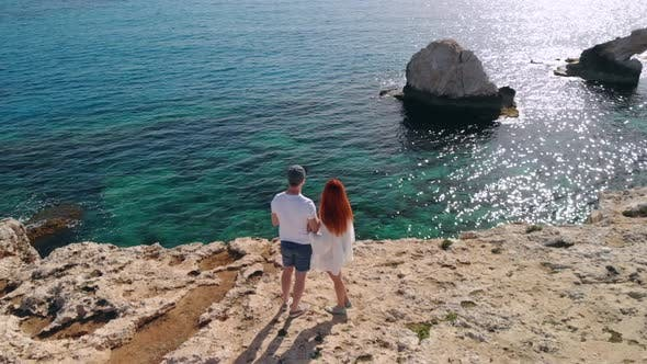 Thumbnail for Aerial View of Couple Standing on Edge of Cliff By Sea