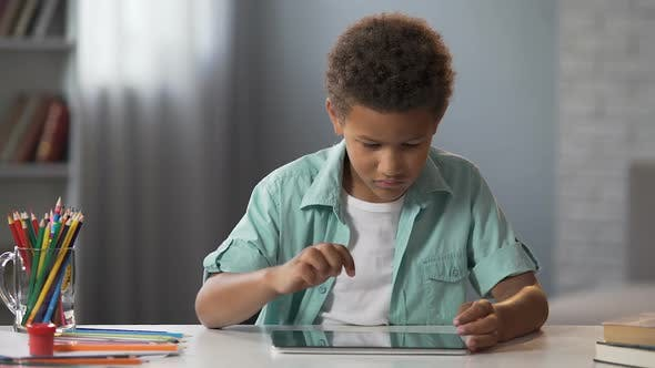 Cover Image for African American Schoolboy Watching His Favorite Educational Show on Tablet