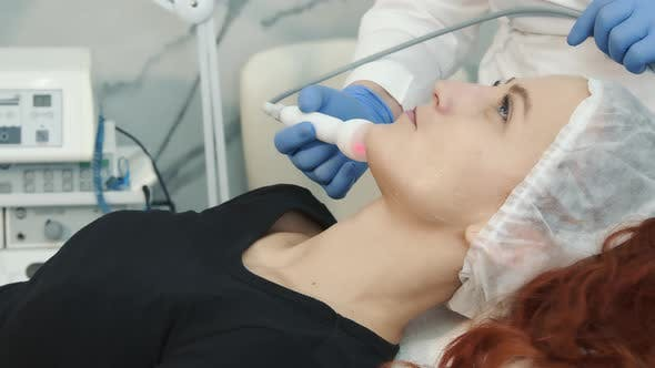 Happy Woman in Profile Lying in a Spa and Undergoing a Procedure To Restore and Rejuvenate the Skin