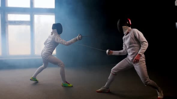 Cover Image for Two Young Women Fencers Having a Training Duel in the Studio