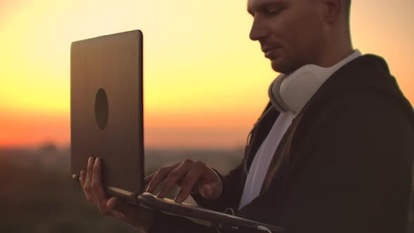 Thumbnail for Standing at Sunset on the Roof with a Laptop and Beer in Headphones Work Remotely and Contemplate
