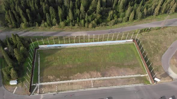 Drone view of biathlon training tracks with athletes training on skiing at offseason