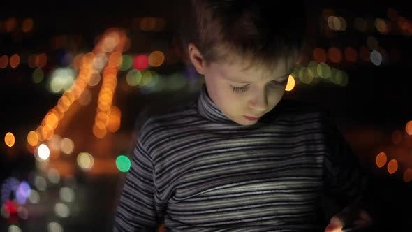 Thumbnail for Young Boy Plays with the Tablet in the Evening