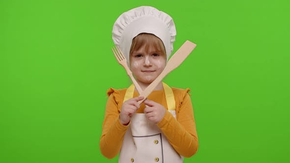 Child Girl Kid Dressed As Cook Chef with Fork and Spatula Showing Symbol of Rejection Disagreement