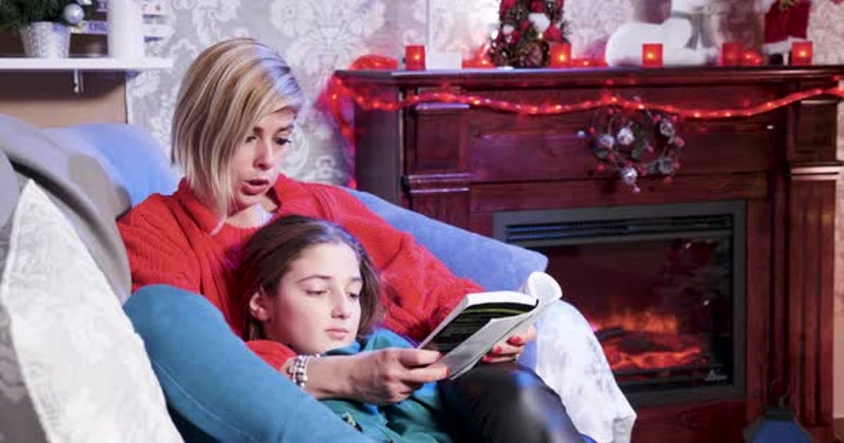 On Christmas Day Young Mother's Reading a Story From a Book