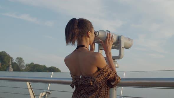 Thumbnail for Woman Looking Through Tourist Telescope at Dawn