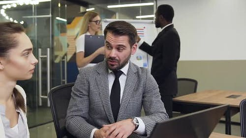 Bearded Businessman which Emotionally Telling to His Considerate Female Colleague